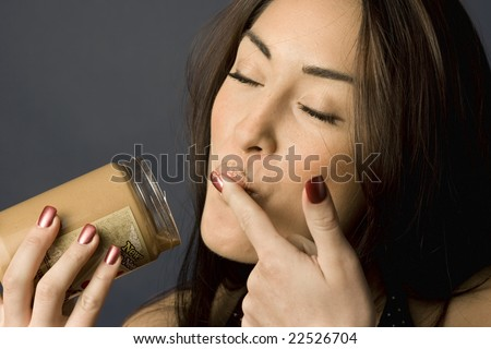 Beautiful woman licking peanut butter off her finger - stock photo