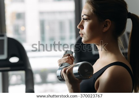 Beautiful woman lifting dumbbell in gym. She training biceps. - stock photo