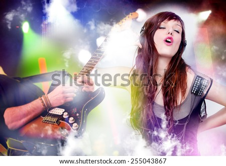 Beautiful woman listening to music with headphones. Live music background with guitar and bright lights on stage. Live music and party concept. - stock photo