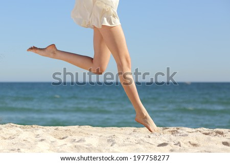 Beautiful woman long legs jumping on the beach with the sea in the background                  - stock photo