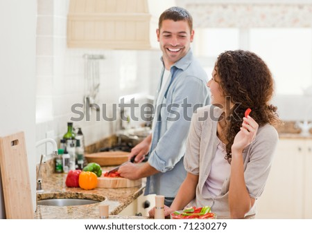Beautiful woman looking at her husband who is cooking at home - stock photo