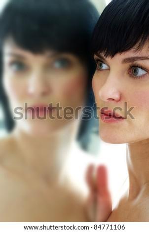 beautiful woman looking in mirror - stock photo