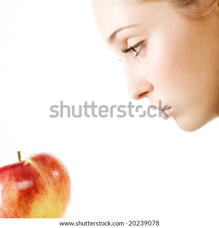 Beautiful woman looking into apple on white background, square composition, shallow DOF. - stock photo