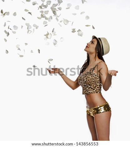 Beautiful woman looks up to the falling rose petals while isolated on a white background. - stock photo