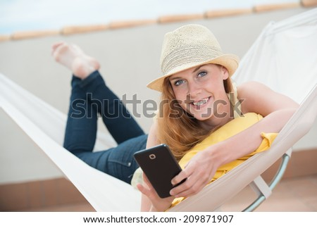 Beautiful woman lying in a hammock with a mobile phone looking up at the camera with a lovely friendly smile - stock photo