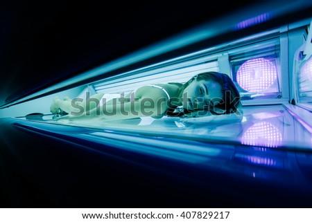 Beautiful woman lying in solarium and sunbathing - stock photo