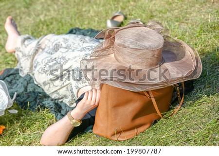 Beautiful woman lying in the garden in a a field - stock photo