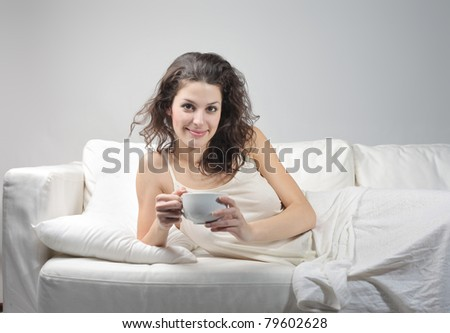 Beautiful woman lying on a sofa and holding a cup of tea - stock photo