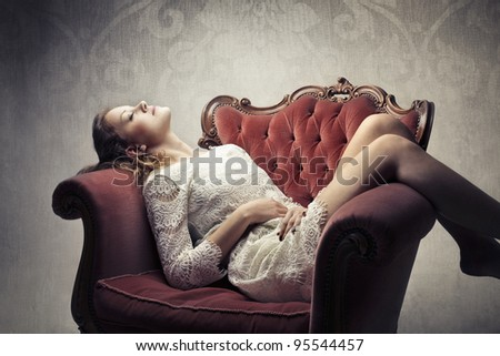 Beautiful woman lying on an armchair with a sensual pose - stock photo