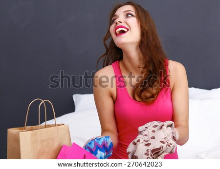 Beautiful woman lying on bed with a laptop and credit card - stock photo