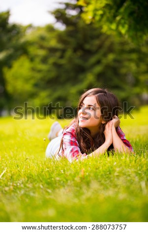Beautiful woman lying on green grass and dreaming - stock photo