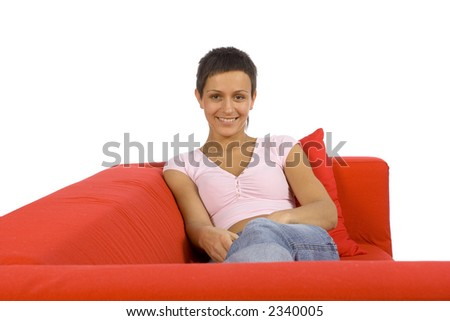 beautiful woman lying on the red sofa - stock photo