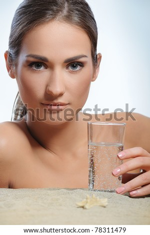beautiful woman lying on the sand and drinks water from glass - stock photo