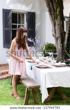 Beautiful woman lying the table, getting ready for the summer outdoor garden party - stock photo