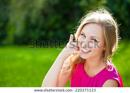 Beautiful woman making a call me gesture - stock photo