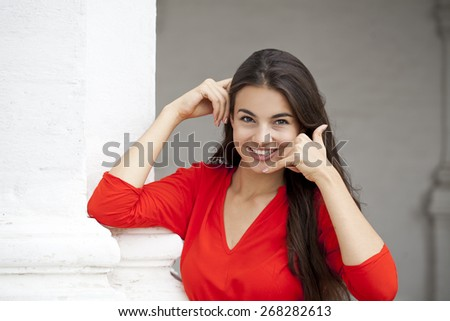Beautiful woman making a call me gesture, happy girl in red dress on white wall background - stock photo