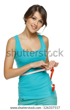Beautiful woman measuring her waist with a measuring tape over white background - stock photo