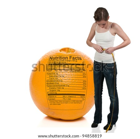 Beautiful woman measuring her waist with a tailors tape in front of an orange - stock photo