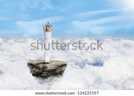 Beautiful woman meditate yoga above clouds - stock photo