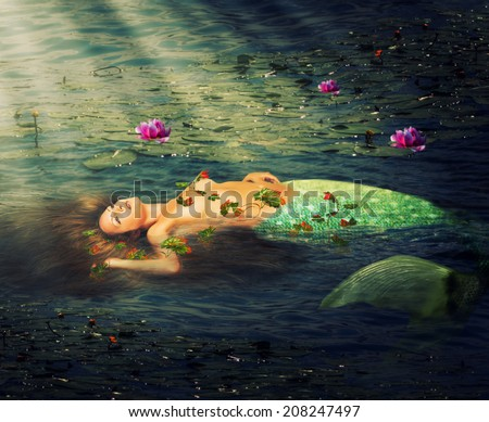 Beautiful woman mermaid with a fish tail resting in the water of the pond of lilies - stock photo