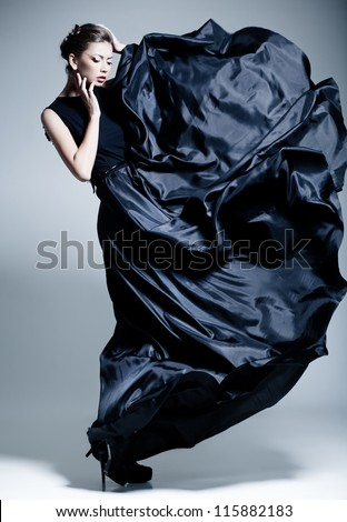 beautiful woman model dressed in an elegant dress in a fashion pose - stock photo