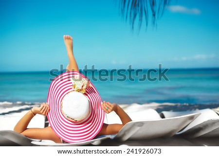 Beautiful woman model sunbathing on the beach chair in white bikini in colorful sunhat behind blue summer water ocean - stock photo