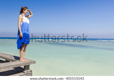 Beautiful woman on a beautiful tropical beach looking somewhere  - stock photo