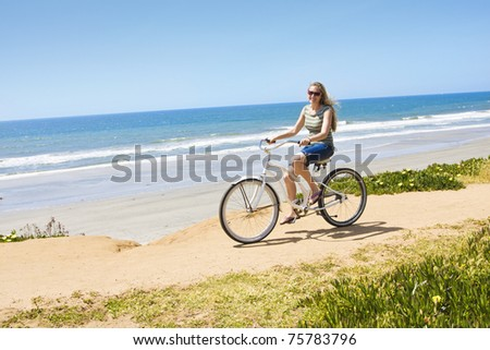 Beautiful Woman on a Bicycle Ride along the beach - stock photo