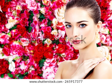 Beautiful woman on a floral background with red and white roses - stock photo