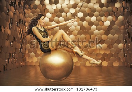 Beautiful woman on a gold ball - stock photo