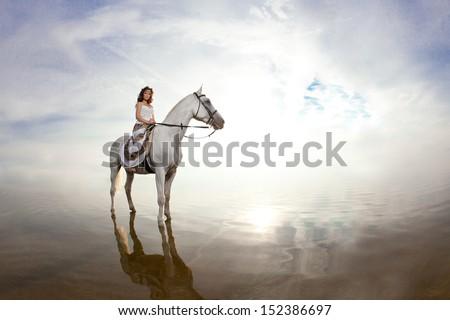 Beautiful woman on a horse. Horseback rider, woman riding horse on beach - stock photo