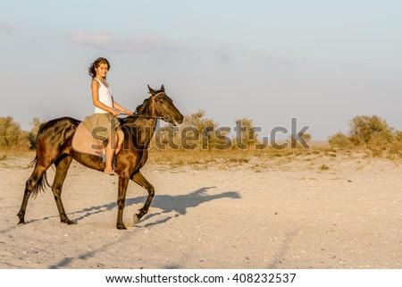 Beautiful woman on a horse. Horseback rider, woman riding horse, sea background - stock photo