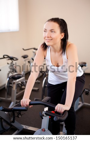 beautiful woman on an exercise bike at the gym - stock photo