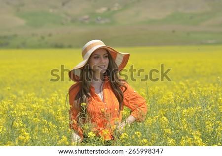 Beautiful woman on blooming rapeseed field - stock photo