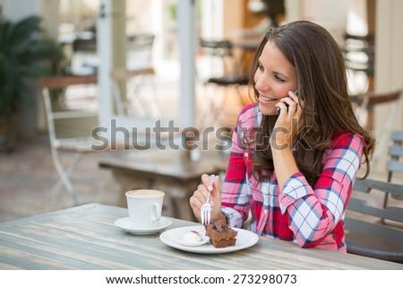 Beautiful woman on phone eating cake - stock photo