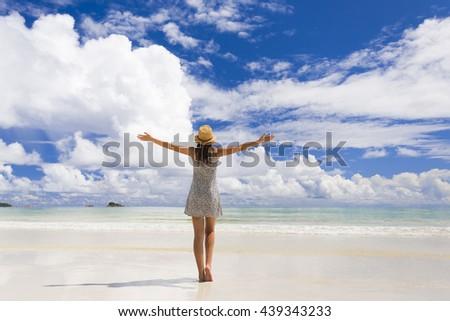 Beautiful woman on the beach enjoying the beauty of Praslin, Seychelles - stock photo