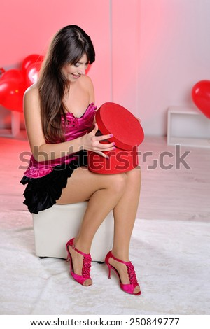 beautiful woman on Valentine's Day in the studio opens gift. - stock photo