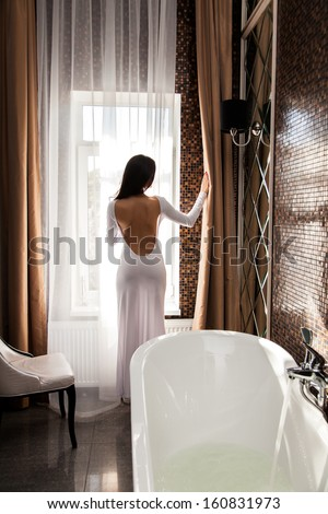 Beautiful woman open the curtain and preparing to take a bath - stock photo