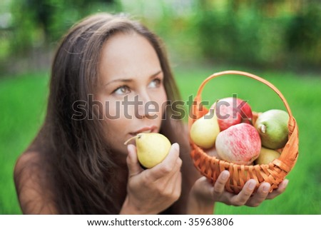 Beautiful woman outdoor with apples and pears in the crib - stock photo
