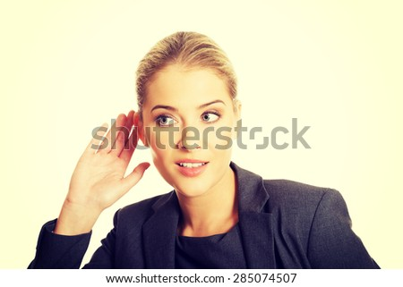 Beautiful woman overhearing a conversation - stock photo
