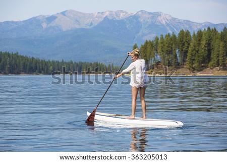 Beautiful woman paddle boarding on scenic peaceful mountain lake - stock photo