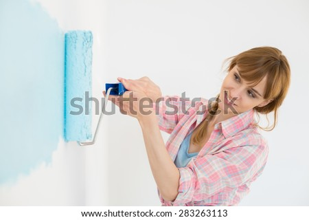 Beautiful woman painting wall with paint roller - stock photo