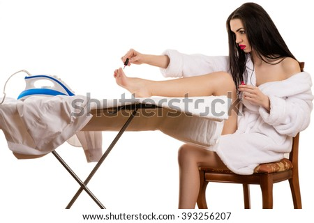 beautiful woman paints the nails on the foot - stock photo