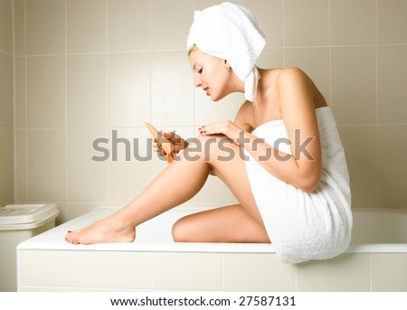 beautiful woman pampering herself in the bathroom after the shower and applying body lotion - stock photo
