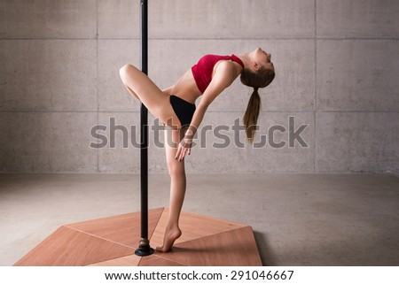 Beautiful woman performing pole dance. Shot with industrial concrete background. - stock photo