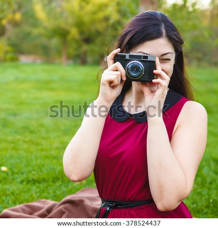 beautiful woman photographed in the park on an old film camera - stock photo