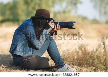 beautiful woman photographer with a camera taking photos - stock photo