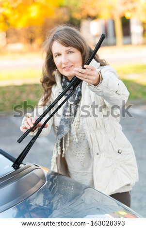 Beautiful woman picking up windscreen wiper and checking it. Focus on hands. - stock photo