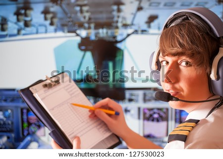 Beautiful woman pilot wearing uniform with epauletes and headset, writting on notepad inside airliner - stock photo
