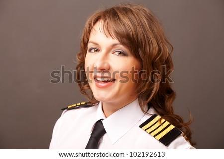 Beautiful woman pilot wearing uniform with epauletes looking ahead, standing - stock photo